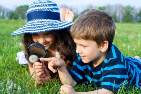 field glass: Kids on the meadow looking to dandelion with a magnifying glass