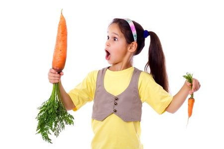little girl surprised: Amazed girl stands with two different sized carrots, isolated on white Stock Photo