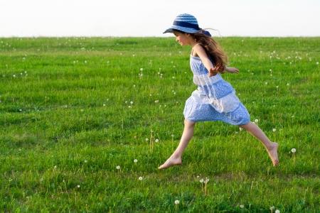 niño corriendo: Chica en el sombrero se ejecuta en prado verde con dientes de león