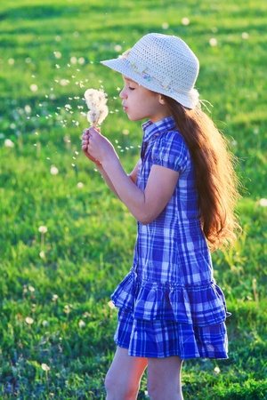 Girl in a hat blowing to bunch of dandelions, standing on a green meadow photo