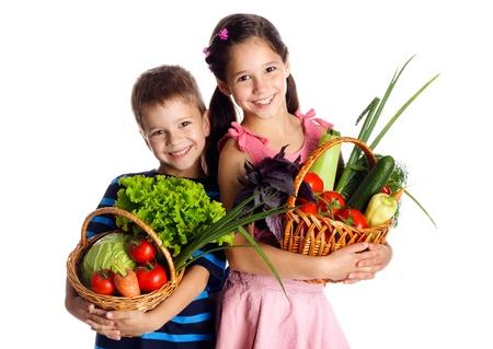 Lachende kinderen met verse groenten in manden, geïsoleerd op wit