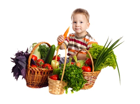 Little boy with fresh vegetables in baskets and carrot in hand, isolated on white