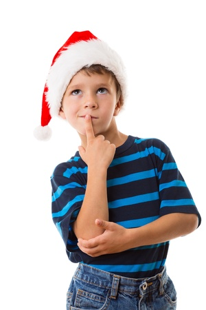 Thoughtful boy in Santa hat, thinking about choice, isolated on white Stock Photo - 21767582