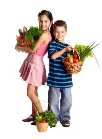 Lachende kinderen staan met verse groenten in manden, geïsoleerd op wit Stockfoto