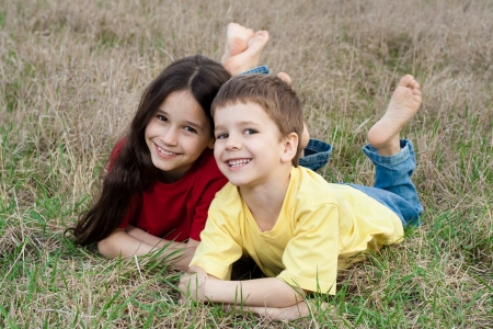 Two smiling kids on the autumn grass photo