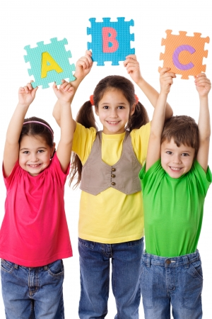 Three kids with colorful letters in raised hands, isolated on white Stock Photo - 22012415