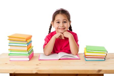 niños estudiando: Muchacha sonriente con la pila de libros en el escritorio, aislado en blanco