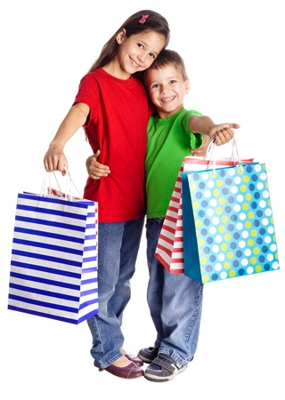 Happy kids standing with shopping bags, isolated on white Stockfoto