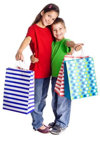 Gelukkig kinderen staan met boodschappentassen, geïsoleerd op wit