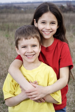 Two smiling kids standing together on the autumn fields, outdoor photo