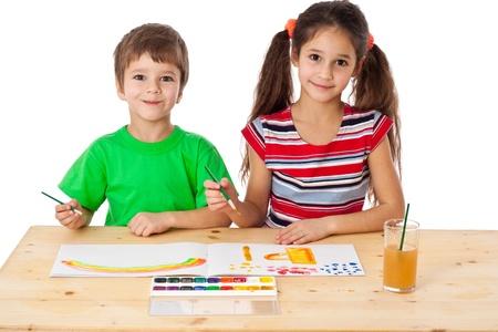 Due sorridente ragazzini al tavolo da disegno insieme, isolato su bianco