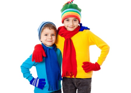 Two smiling kids in winter clothes together, isolated on white