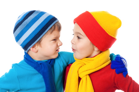 Two speaking kids in winter clothes showing a different emotions, isolated on white