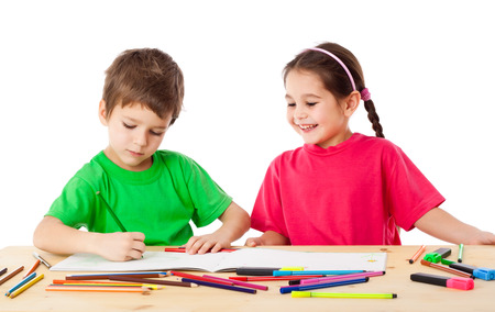 depict: Two smiling little kids at the table draw with crayons, isolated on white Stock Photo