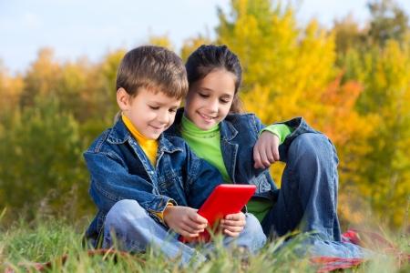 Twee lachende kinderen met tablet pc zittend op het grasveld herfst, buitenshuis