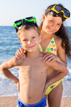 Two happy kids in diving masks standing together on the beach photo