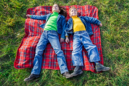 Two happy kids lying on the green grass meadow with closed eyes photo