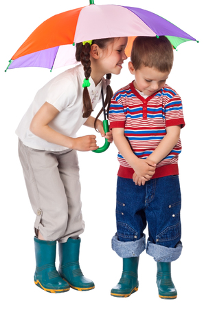 Two little children together under colorful umbrella photo