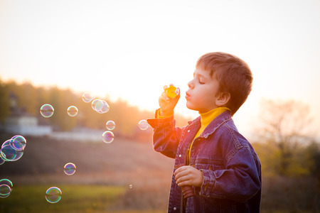 Smiling boy blowing the soap bubbles on the autumn landscape against sunset photo