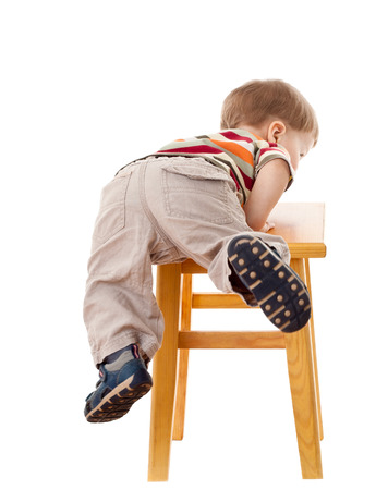 Little boy climbing on stool, isolated on white photo