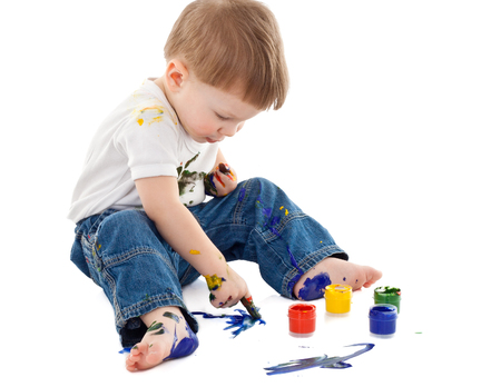little boy painting on the floor and stained in paint on white background.