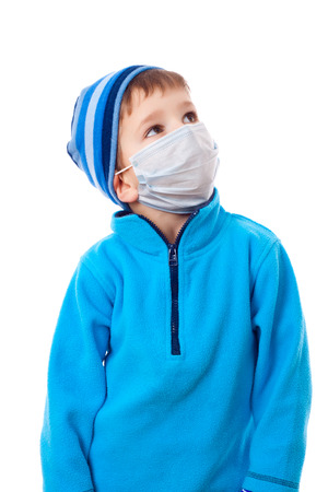 sick kid: Boy in winter clothes and protective medical mask looking sideways, isolated on white