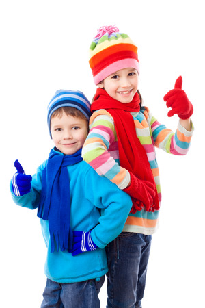 Two kids in winter clothes and thumbs up sign, isolated on white