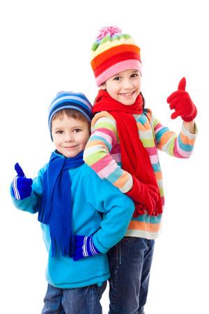 Twee kinderen in de winter kleding en thumbs up teken, geïsoleerd op wit Stockfoto