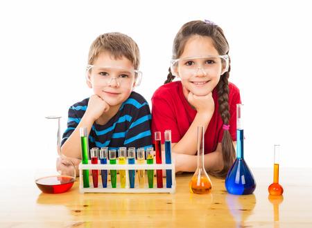 Twee lachende kinderen op het bureau met chemische apparatuur, geïsoleerd op wit