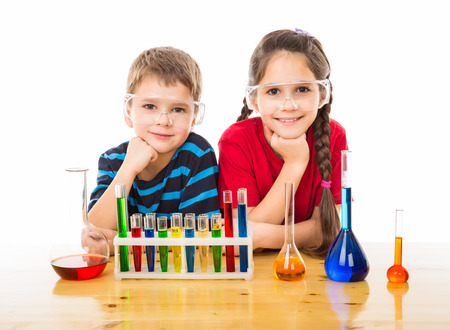 Two smiling kids on the desk with chemical equipment, isolated on white