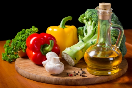 fresh vegetables with bottle of oil on cutting board photo