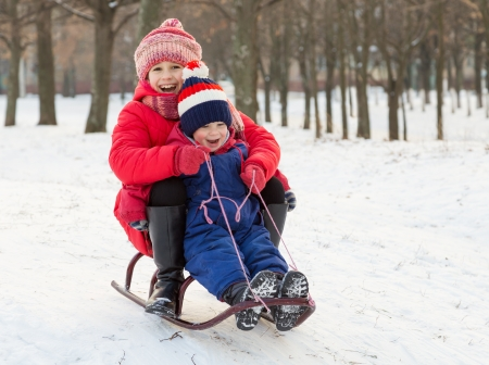 sledding: Two happy kids in winter clothes on the sled Stock Photo
