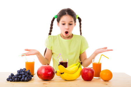 little girl surprised: surprised girl chooses fruits and juices, isolated on white