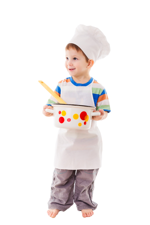 Smiling little cook standing with ladle and pan, isolated on white photo