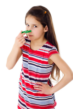 nose plugs: Displeased girl with clothespins on his nose, isolated on white