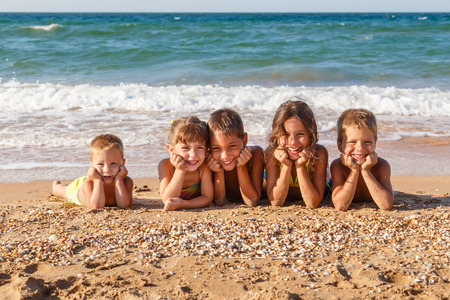 Five smiling kids enjoying on the beach photo