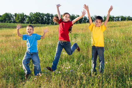 Happy jumping kids on green field, outdoors photo