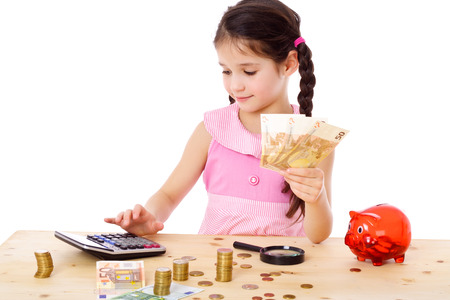 Little girl at the table counts money, isolated on white Stockfoto