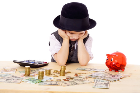 Sad boy in black hat at the table with pile of money, isolated on white photo