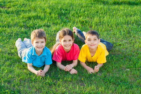 Group of smiling kids lying on the green grass meadow photo