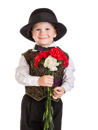 Smiling boy in hat standing with a bouquet of carnations, isolated on white photo