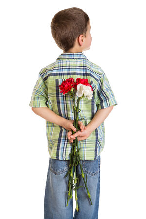 Little boy turned back and hiding bouquet of carnations behind itself, isolated on white photo