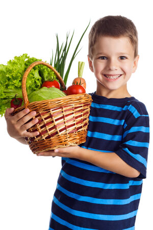Smiling boy standing with fresh vegetables in the basket, isolated on white photo