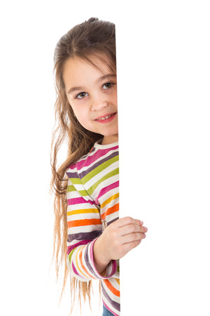 Smiling girl peek out from vertical empty white banner, isolated on white photo