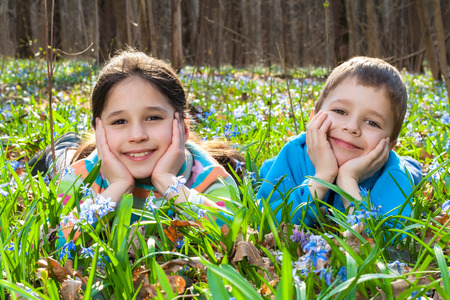 Two kids lying among the bluebells in the forest photo