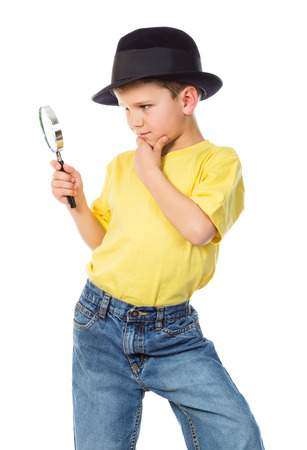 investigating: Boy in black hat standing with magnifying glass, isolated on white