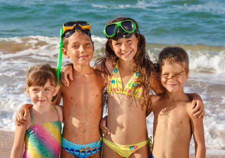 Four smiling kids enjoying on the beach photo