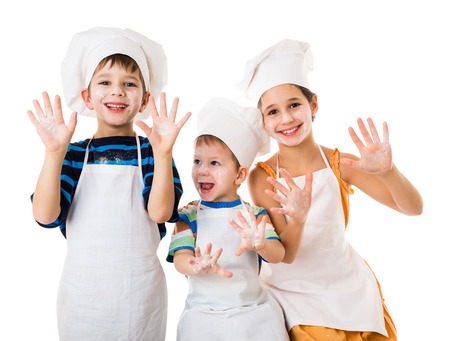 Three young chefs with raised hands in flour, isolated on white