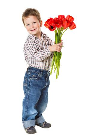 dar un regalo: Niño feliz con el ramo de tulipanes rojos, aislados en blanco