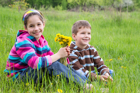 Two kids with bouquet of dandelions sitting on green meadow photo